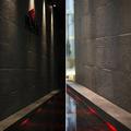 Giochi di luce e acqua lungo pareti rivestite da gres porcellanato effetto pietra