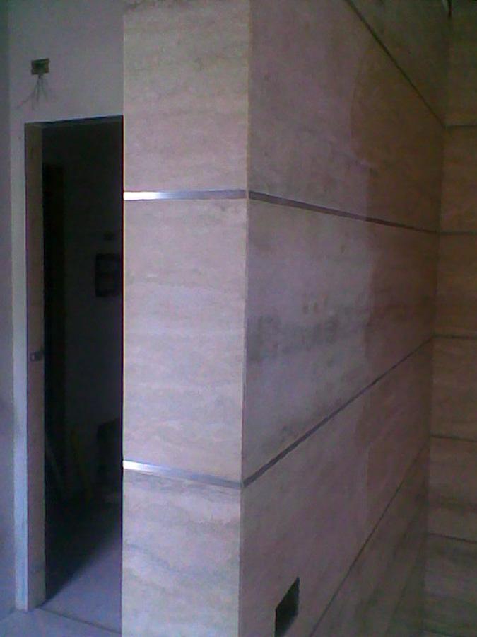 bagno in travertino classico con liste in acciaio satinato