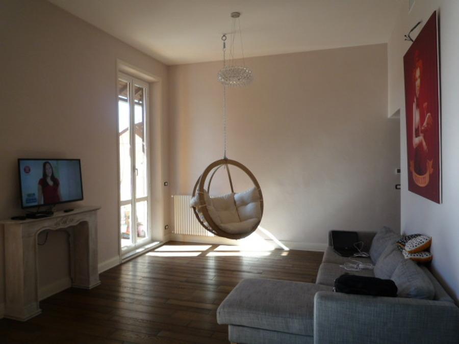 soggiorno con pavimento in parquet e sedia sospesa