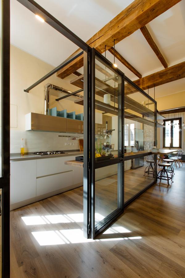 Una parete vetrata per delimitare/unire gli spazi della zona giorno