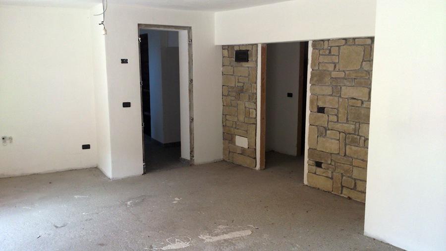 Foto salone con rivestimento in pietra di costruzioni for Salone con parete in pietra