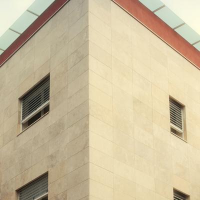 Particolare facciata ventilata in travertino e pensilina in vetro