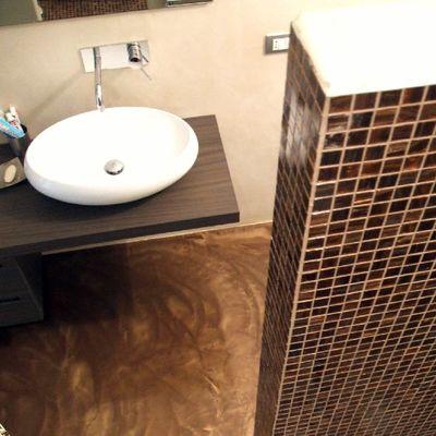 Bagno con pavimento materico e rivestimento mosaico