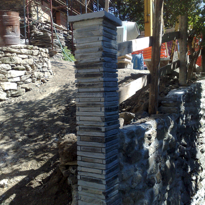 Colonna di cemento rivestita con pietre di recupero