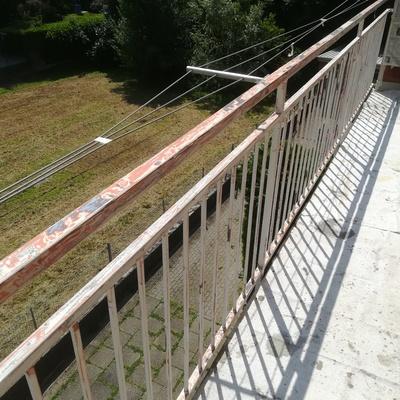 Pulizia meccanica e manuale ringhiera balcone prima dell' applicazione totale di una mano di antituggine.
