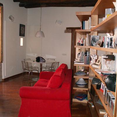 Particolare della libreria-divisorio e del divano, visti dall'ingresso dell'appartamento