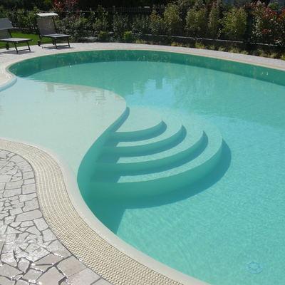 piscina a forma libera, bordo sfioratore, spiaggia interna con scala tonda