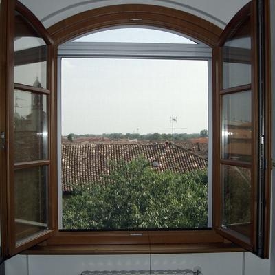 Zanzariera ad apertura verticale con sopraluce fisso arcato