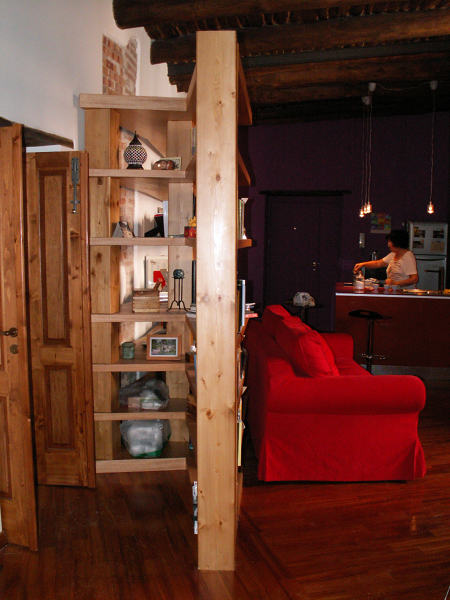 Parete divisoria per nascondere la porta del bagno, realizzata con una libreria in legno lamellare