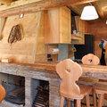Il caminetto in pietra e il piano ricavato dalle vecchie travi del fienile. Sullo sfondo la cucina