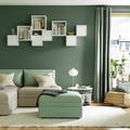 Salotto con parete verde e mobili bianchi