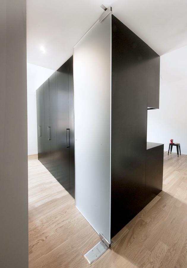 Dettaglio del volume nero sul lato della zona notte con armadiature e porta in vetro acidato.