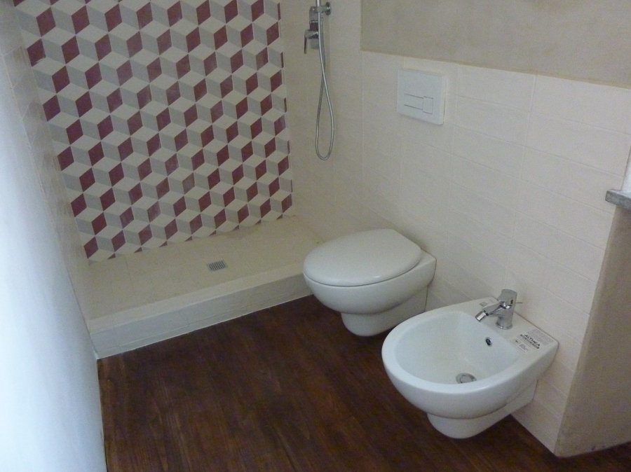 """Bagno con doccia """"retro"""" e pavimento in legno"""