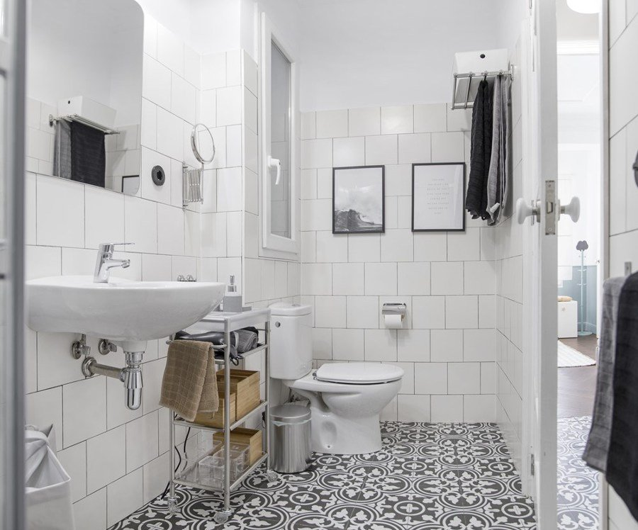 Bagno con piastrelle bianche e pavimento decorato