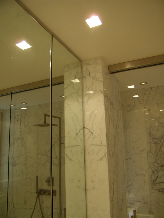 Box doccia in marmo di Carrara, pareti e porte in cristallo.