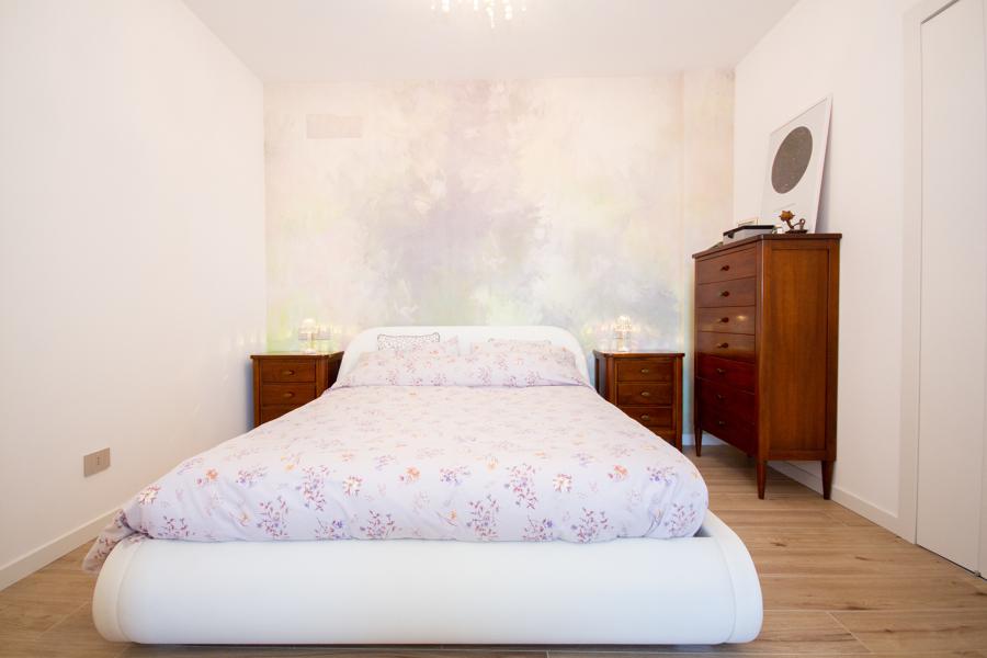 camera da letto matrimoniale con carta da parati dietro la testata
