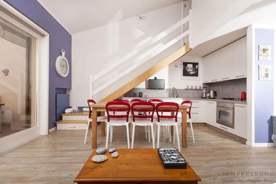Cucina angolare arredata con mobili su misura per sfruttare lo spazio sottoscala