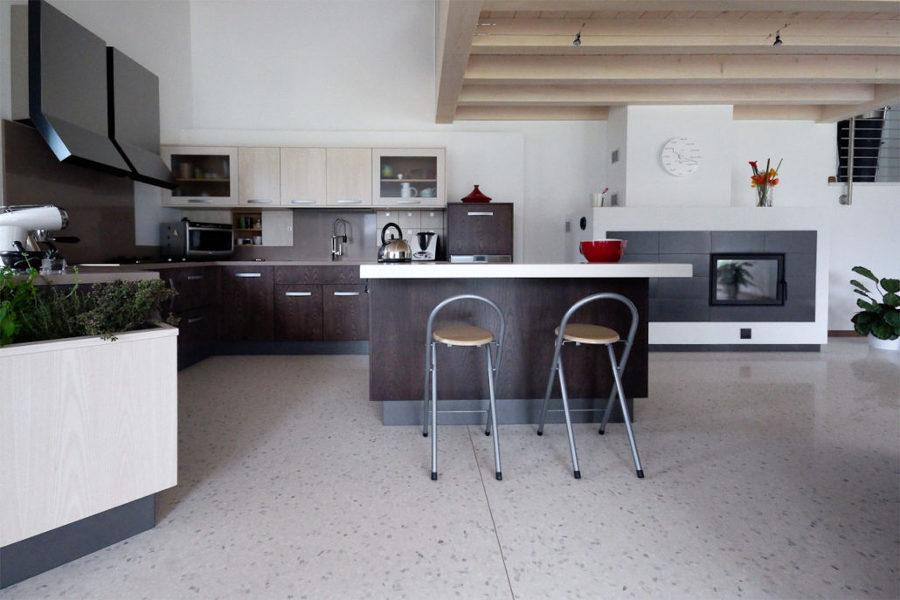Cucina open space con mobili in legno scuro