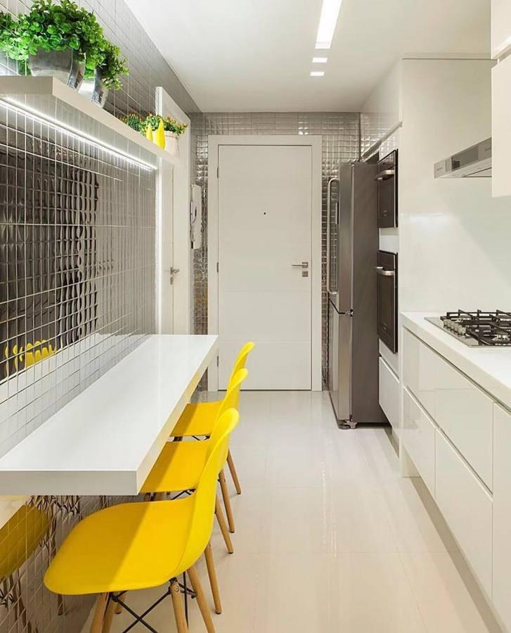 Cucina stretta e lunga con mobili bianchi e dettagli a contrasto