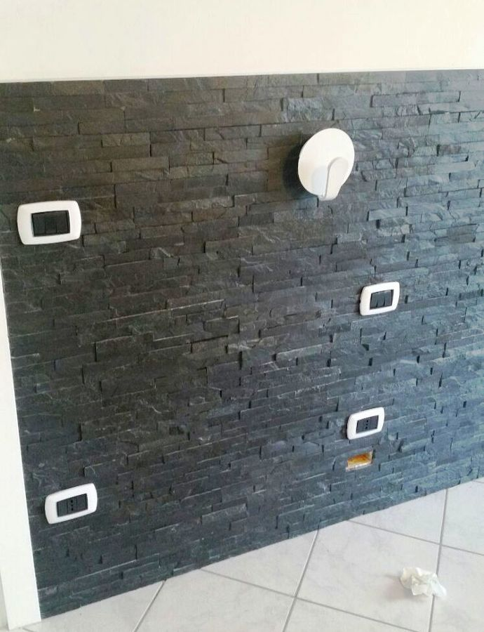 Foto parete rivesito con palcche di pietra in camera da - Parete in pietra camera da letto ...