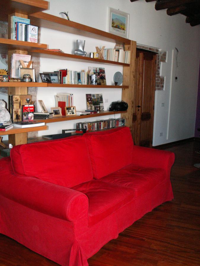 Particolare del divano del salone e sullo sfondo l'ingresso del ropostiglio