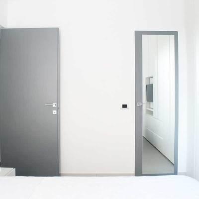 Camera da letto e porta a specchio che chiude il bagno di servizio