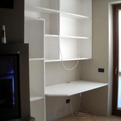 Librerie sospese, con legnaia e piano scrivania; pensile bagno