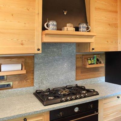 La cucina con i mobili in larice e il piano in pietra