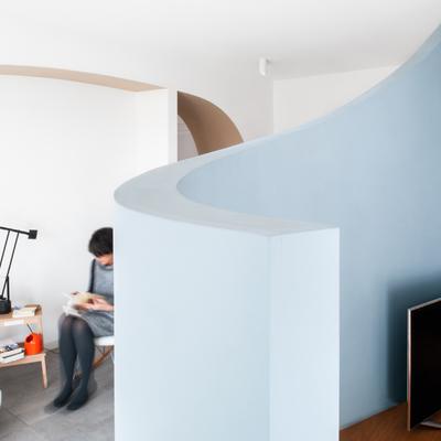 Un appartamento ristrutturato con colori tenui e forme sinuose