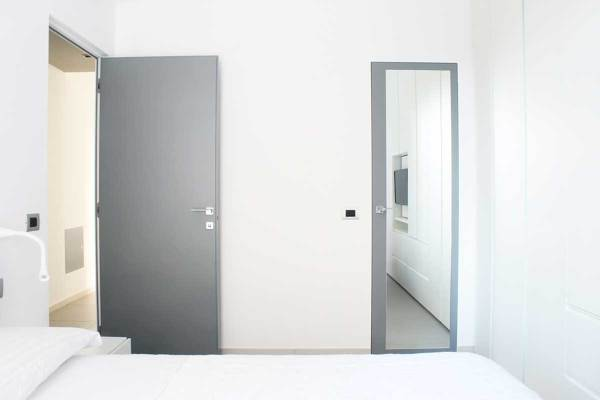 Foto camera da letto e porta a specchio che chiude il bagno di servizio di francesco ruffa - Specchio camera letto ...