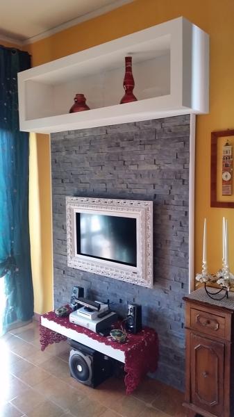 Foto con rivestimento in pietra in gesso e cornice in for Parete in pietra con tv