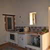 Angolo cottura con cucina in muratura, realizzata con rivestimento di lastre di cotto artigianale su misura per il piano