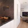 Parete attrezzata ingresso e piano cucina in pietra che integra la tv