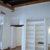 Sala d'ingresso con libreria in muratura e mensole di legno laccate, di recupero.