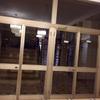 Riduzione di un'apertura con vetrina incassata in cartongesso e vetrata in alluminio con porte automatiche